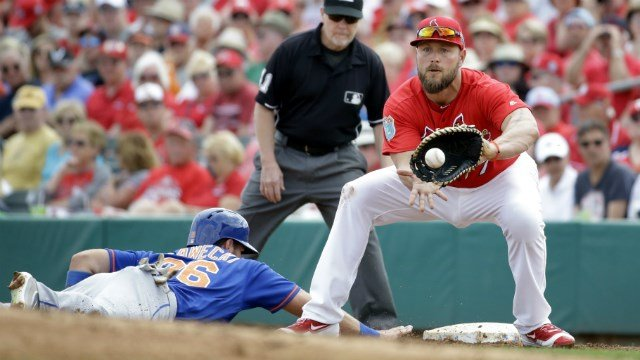 St. Louis Cardinals first baseman Matt Holliday, right, holds New York Mets base runner Kevin Plawecki on during the third inning of an exhibition spring training baseball game Monday, March 7, 2016, in Jupiter, Fla. (AP Photo/Jeff Roberson)