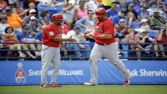 St. Louis Cardinals' Matt Adams, right, is congratulated by third base coach Jose Oquendo after hitting a two-run home run during the fourth inning of an exhibition spring training baseball game against the New York Mets Thursday, March 10, 2016, in Port