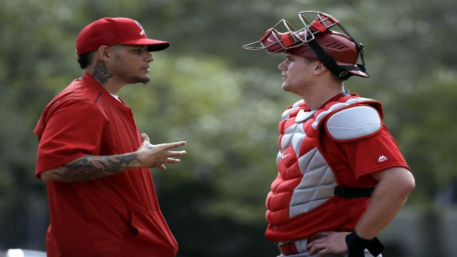 St. Louis Cardinals catcher Yadier Molina, left, talks with fellow catcher Carson Kelly during spring training baseball practice Sunday, Feb. 21, 2016, in Jupiter, Fla. (AP Photo/Jeff Roberson)