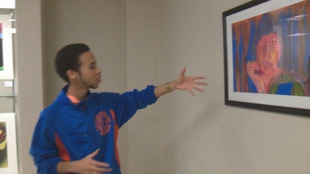Andra Lang shows off one of his paintings. (Credit: KMOV)
