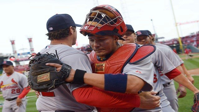 St. Louis Cardinals catcher Yadier Molina hugs manager Mike Matheny after they defeated the Cincinnati Reds 1-0 in a baseball game, Monday, March 31, 2014, on opening day in Cincinnati. (AP Photos)
