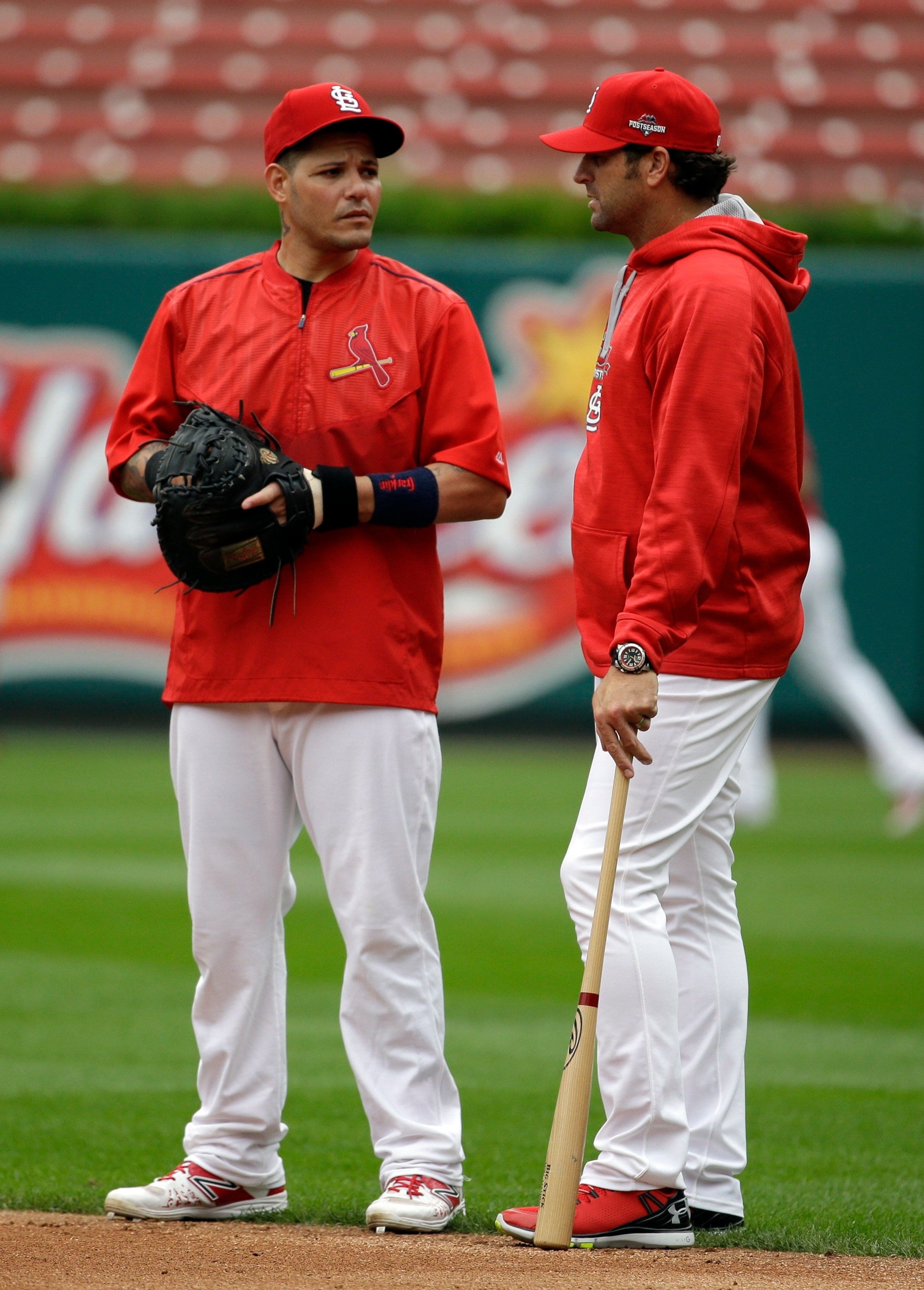 Yadier Molina talks with manager Mike Matheny during baseball practice on Wednesday, Oct. 7, 2015, in St. Louis, ahead of Game 1 of the NLDS. (AP Photo/Jeff Roberson)