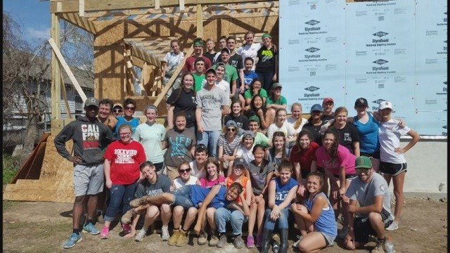 Students pose for a photo in front of a home they were rebuilding. (Credit: KMOV)