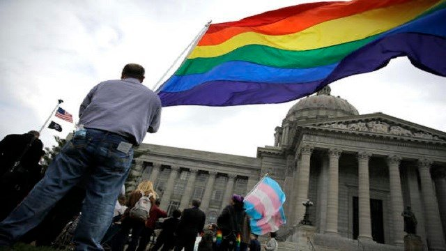 A gay-rights supporter holds a flag outside the Capitol in Jefferson City. Republican lawmakers have advanced measures in about a dozen states that could strengthen religious protections . (AP Photos)