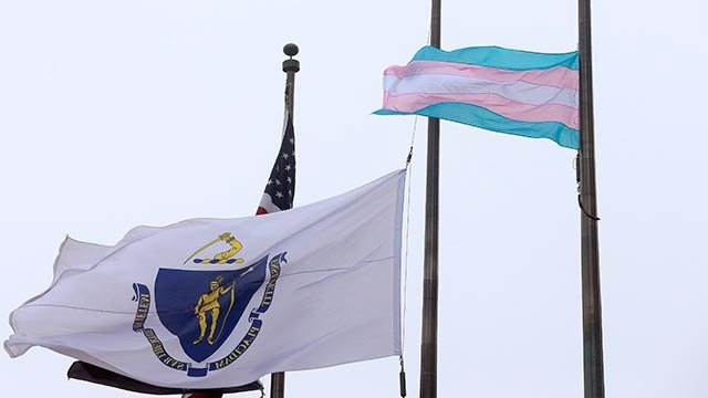 A flag representing the transgender community, right, flies next to the Massachusetts state flag, left, and an American flag, behind, in front of Boston City Hall, Monday, May 2, 2016, in Boston. (Credit: AP Photo / Steven Senne)