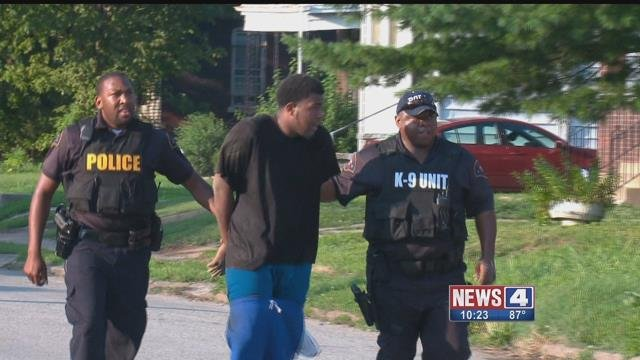 A man who briefly escaped from police custody and ran away in East St. Louis, is escorted by officers to a police car on July 20. Credit: KMOV