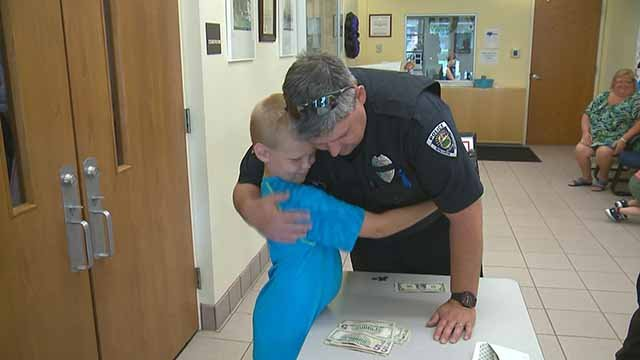 One of the Mayer brothers hugs a Ballwin police officer. The brothers set up a lemonade stand to help Officer Michael Flamion. Credit: KMOV