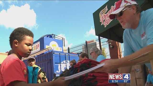 A volunteer with Cardinals Care hands a notebook to a child at an event where the Cardinals handed out school supplies to under privileged kids. Credit: KMOV