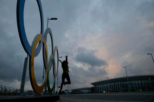 Monalisa Paduin poses for photos in front of the Olympic rings set up outside the Olympic Aquatics Stadium at Olympic Park ahead of the 2016 Summer Olympics in Rio de Janeiro, Brazil, Tuesday, Aug. 2, 2016. (AP Photo/Jae C. Hong)