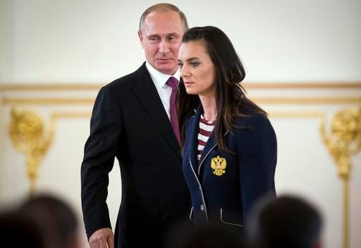 Russian President Vladimir Putin, left, smiles after Russia's pole vaulter Yelena Isinbayeva spoke at the Kremlin, in Moscow, Russia, Wednesday, July 27, 2016 during a reception for the Russia's Olympics team. (AP Photos)