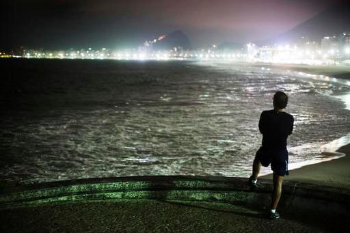 A pedestrian looks out toward Copacabana Beach ahead of the upcoming 2016 Summer Olympics in Rio de Janeiro, Brazil, Tuesday, Aug. 2, 2016. (AP Photo/David Goldman)
