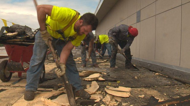 Roofers working for CMT Roofing which just got a much need boost in capital. (Credit: KMOV).