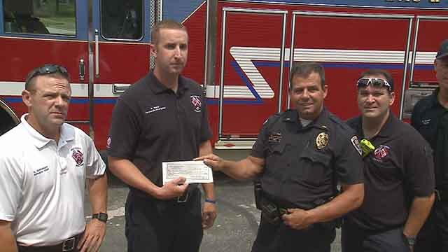 West County Fire and EMS presented a check for $15,000 to the Ballwin Police Department for Officer Mike Flamion and his family. Credit: KMOV