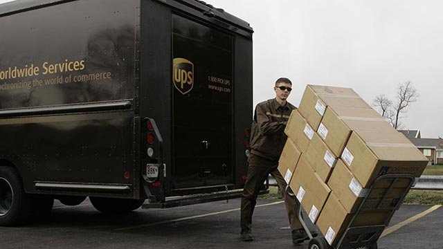 UPS driver pushes a load of packages (Credit: AP Images)
