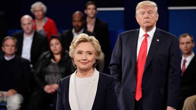 Democratic presidential nominee former Secretary of State Hillary Clinton (L) and Republican presidential nominee Donald Trump listen during the town hall debate at Washington University on October 9, 2016 in St Louis, Missouri.  Photo by Saul Loeb-Pool