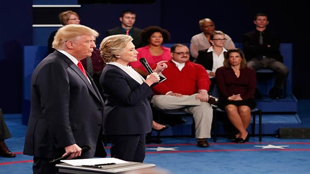 Republican presidential nominee Donald Trump, left, listens as Democratic presidential nominee Hillary Clinton speaks during the second presidential debate at Washington University in St. Louis, Sunday, Oct. 9, 2016. (Rick T. Wilking/Pool via AP)