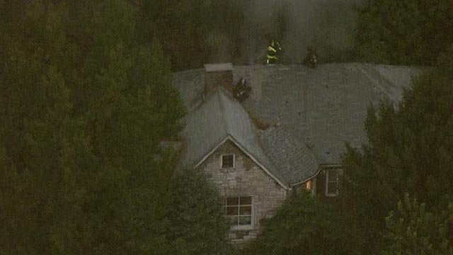 Firefighters on top on home at Eichelberger & Wherry Thursday morning (Credit: KMOV)