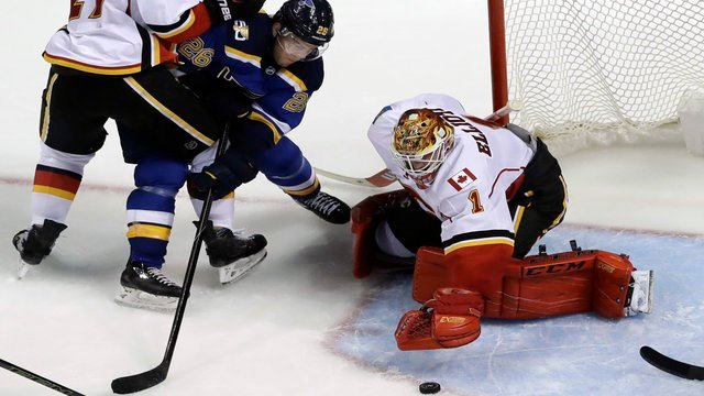 St. Louis Blues' Paul Stastny, left, and Calgary Flames goalie Brian Elliott reach for a loose puck during the third period of an NHL hockey game Tuesday, Oct. 25, 2016, in St. Louis. The Flames won 4-1. (AP Photo/Jeff Roberson)