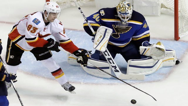 Calgary Flames' Sam Bennett (93) reaches for a loose puck as St. Louis Blues goalie Carter Hutton defends during the second period of an NHL hockey game Tuesday, Oct. 25, 2016, in St. Louis. (AP Photo/Jeff Roberson)
