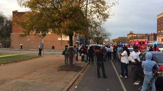 Crowds gather near the scene of a fatal shooting at the intersection of Grand and Sullivan Saturday evening. Credit: KMOV