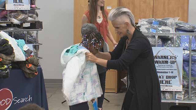 Brenda Warner, the wife of Kurt Warner, presents a coat to a child. Credit: KMOV