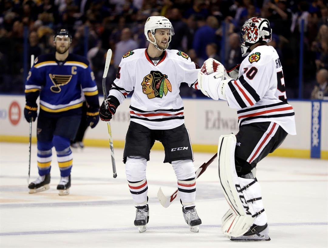 Chicago Blackhawks' Niklas Hjalmarsson and goalie Corey Crawford celebrate as St. Louis Blues' Alex Pietrangelo watches following an NHL hockey game Wednesday, Nov. 9, 2016, in St. Louis. The Blackhawks won 2-1 in overtime. (AP Photo/Jeff Roberson)