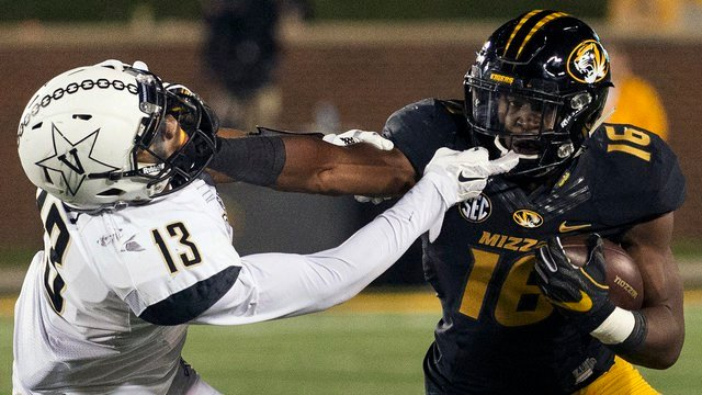 Missouri running back Damarea Crockett, right, grapples with Vanderbilt's LaDarius Wiley, left, while running the ball during the fourth quarter of an NCAA college football game Saturday, Nov. 12, 2016, in Columbia, Mo. (AP Photo/L.G. Patterson)