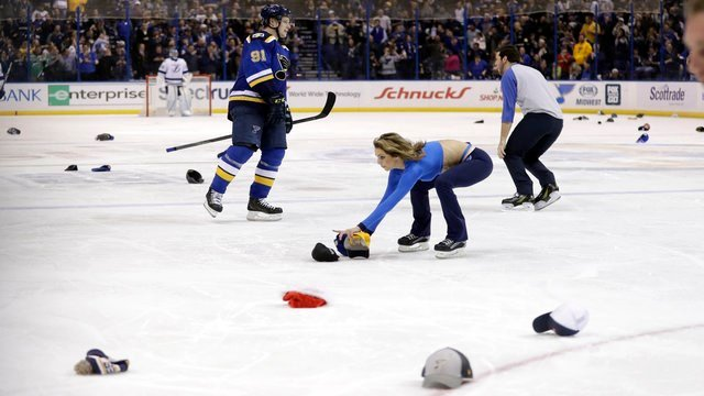 St. Louis Blues' Vladimir Tarasenko skates as workers pick up hats thrown onto the ice by fans in celebration after Tarasenko's third goal of an NHL hockey game against the Tampa Bay Lightning on Thursday, December 1, 2016. (AP Photo/Jeff Roberson)