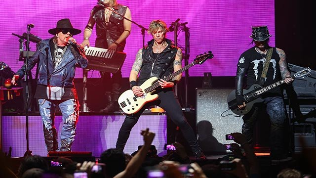 In this April 23, 2014 file photo, Axl Rose, from left, Duff McKagan and DJ Ashba of Guns N' Roses perform on stage at the 6th Annual Revolver Golden Gods Award Show at Club Nokia in Los Angeles. (Photo by Paul A. Hebert/Invision/AP, File)