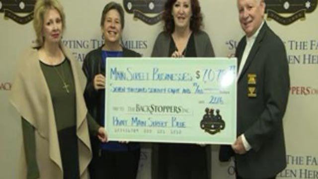 Main Street Businesses present check to BackStoppers (Credit: KMOV)