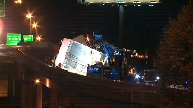 Crews working to upright a semi-truck on the ramp from NB I-55 to the Poplar Street Bridge (Credit: KMOV)
