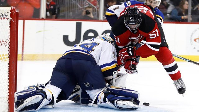 New Jersey Devils center Sergey Kalinin (51), of Russia, goes airborne as St. Louis Blues goalie Jake Allen (34) stops a shot during the second period of an NHL hockey game, Friday, Dec. 9, 2016, in Newark, N.J. (AP Photo/Julio Cortez)