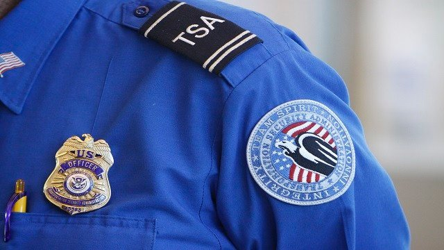 The badge and TSA logo patch are seen on the uniform of a Transportation Security Administration employee at one of the security checkpoints inside Lambert- St. Louis International Airport Thursday, Oct. 7, 2010, in St. Louis. (AP Photo/Jeff Roberson)
