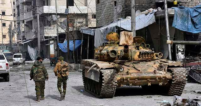 Two Syrian soldiers pass by a tank where government forces have captured wide areas in eastern Aleppo, Syria, Monday, Dec. 12, 2016. (SANA via AP)