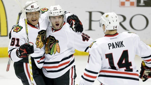 Chicago Blackhawks' Vinnie Hinostroza (48) celebrates with teammates Marian Hossa (81) and Richard Panik (14) after scoring a goal in the third period of an NHL hockey game against the St. Louis Blues, Dec. 17, 2016, in St. Louis. (AP Photo/Tom Gannam)