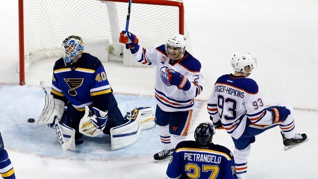 Edmonton Oilers' Ryan Nugent-Hopkins celebrates alongside teammate Andrej Sekera after scoring during overtime of an NHL hockey game Monday, Dec. 19, 2016. (AP Photo/Jeff Roberson)