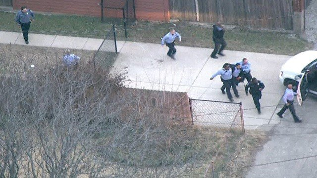 An officer was rushed to a patrol car after being shot in the hand (KMOV)