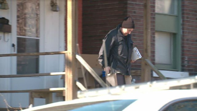 An FBI agent carries out items from a home that is connected to Juan Thompson, who is accused of committing bomb threats to Jewish Community Centers (KMOV).