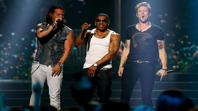 Tyler Hubbard, left, and Brian Kelley, right, of Florida Georgia Line perform with Nelly, center, during the Miss USA 2014 pageant in Baton Rouge, La., Sunday, June 8, 2014. (AP Photo/Jonathan Bachman)