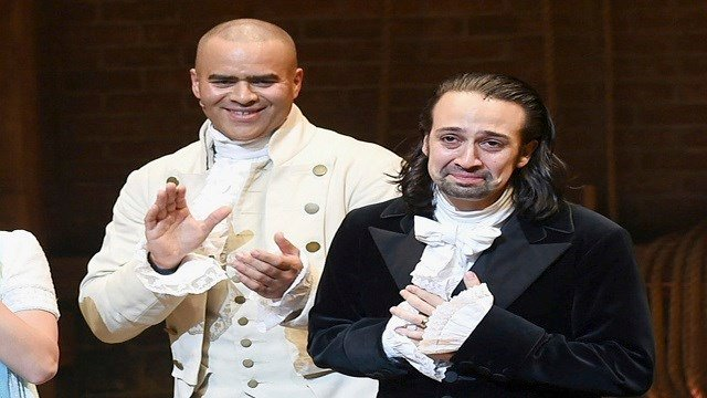 """In this July 9, 2016 file photo, actor and """"Hamilton"""" creator Lin-Manuel Miranda, right, takes his final performance curtain call with cast member Christopher Jackson at the Richard Rogers Theatre in New York. (Credit: Evan Agostini/Invision/AP, File)"""