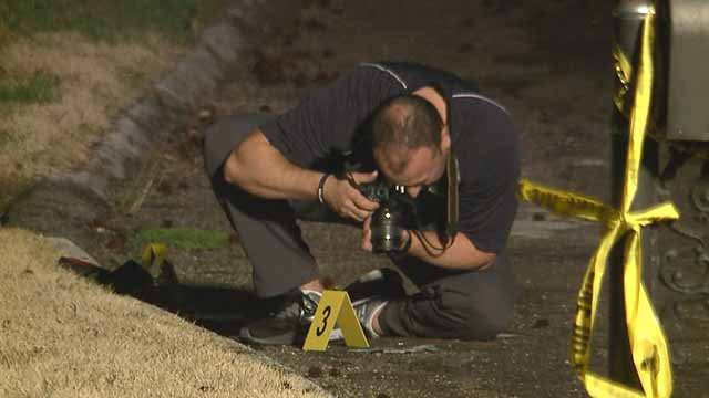 A photographer takes evidence photos at the scene of a shooting on Carole Lane in Frontenac Monday. Credit: KMOV
