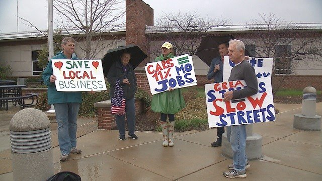 """Residents stood outside the open house with signs that said """"We love cars"""" and """"great streets = slow streets.""""  (Credit: KMOV)"""