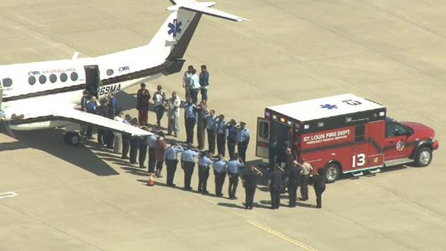 Police lined the entrance to the officer's plane before it took off Wednesday (Credit: KMOV)