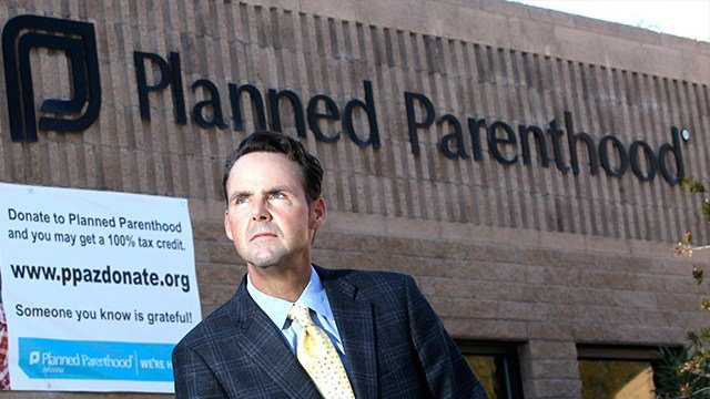 In this photo taken Sunday, Jan. 23, 2011, Bryan Howard, President and CEO of Planned Parenthood Arizona, Inc., poses in front of a Planned Parenthood facility in Tucson, Ariz. (AP Photo/Ross D. Franklin)