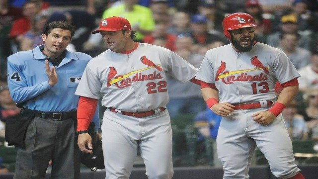 St. Louis Cardinals manager Mike Matheny holds back Matt Carpenter (13) as he talks to hoe plate umpire John Tumpane after Carpenter was ejected for arguing a called strike three during the seventh inning of a baseball game Sunday. (AP Photo/Morry Gash)