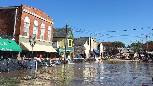 Store owners check the sandbag walls in front of their stores on Main St. in Eureka, Mo. (Credit:Theresa Arnett/UPI)