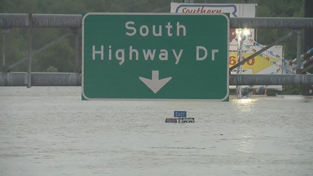 Road signs and floodwaters in Valley Park Wednesday (Credit: KMOV)