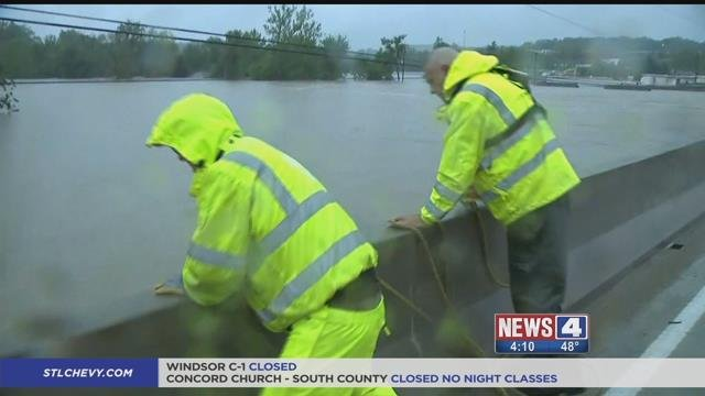 Two surveyors from the USGS measure floodwaters in Fenton.  Credit: KMOV