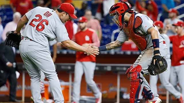 St. Louis Cardinals relief pitcher Seung-Hwan Oh (26) of South Korea, and catcher Yadier Molina celebrate after the Cardinals defeated the Miami Marlins 6-5 during a baseball game, Tuesday, May 9, 2017, in Miami. (AP Photo/Wilfredo Lee)