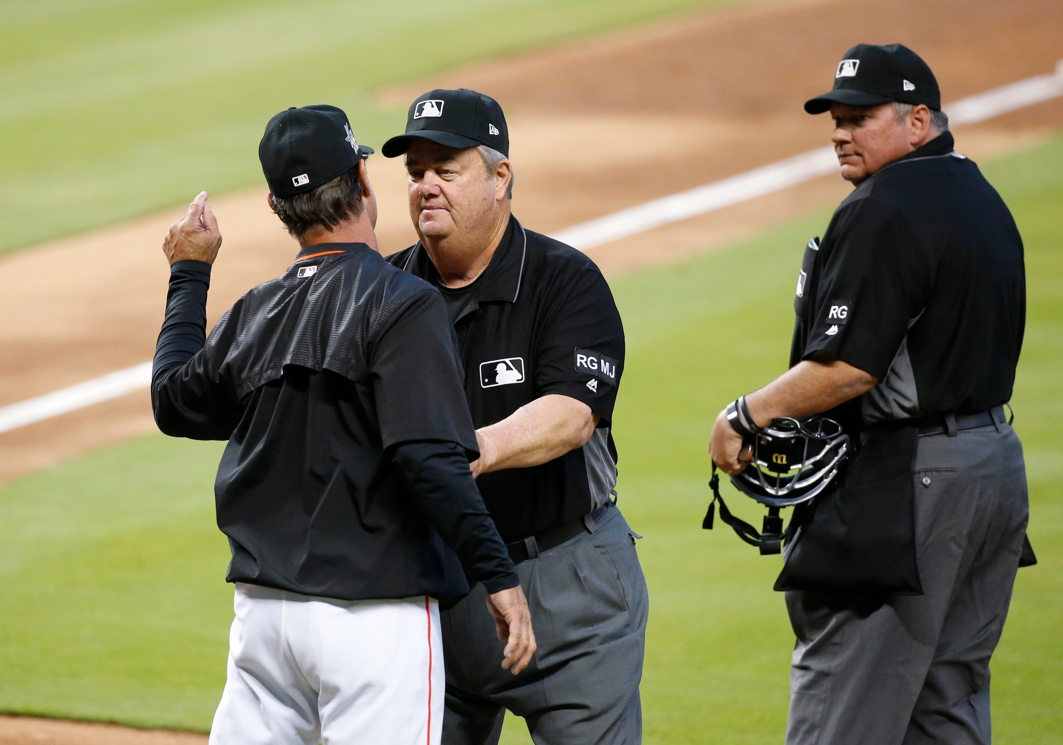Don Mattingly is held back by third base umpire Joe West, as he argues with home plate umpire Hunter Wendelstedt at the end of the second inning of a baseball game against the St. Louis Cardinals, Monday. (AP Photo/Wilfredo Lee)